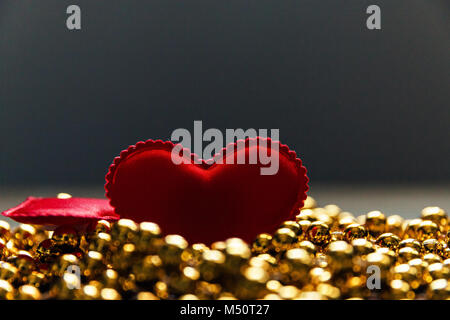 red heart on the Golden beads. - Stock Photo