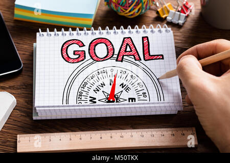 Man Drawing Compass Goal Guidance Concept In Notepad - Stock Photo