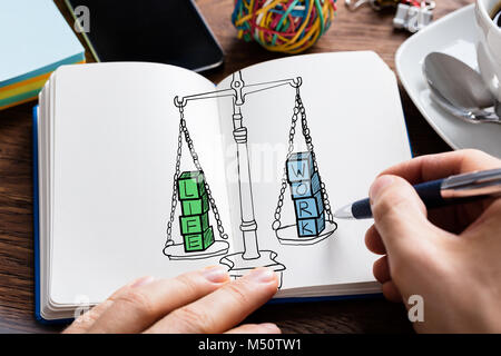 Man Drawing Work Life Balance Concept At Desk - Stock Photo