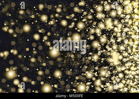 Golden snowflakes swirling on a black background. - Stock Photo