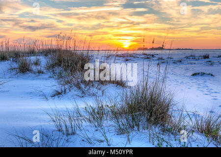 A colorful sunset over the seaoats and dunes on Fort Pickens Beach in the Gulf Islands National Seashore, Florida. - Stock Photo