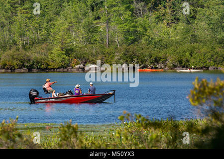 Families engage in recreational boating fishing and kayaking on Squam Lake in Moultonborough, NH, USA. - Stock Photo