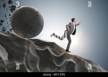 Businessman running away from falling rolling stone - Stock Photo