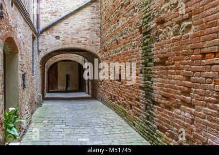 Alley with brick walls in an old village - Stock Photo