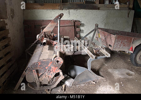 Old farm machinery left at the back of a barn slowly rusting away. - Stock Photo