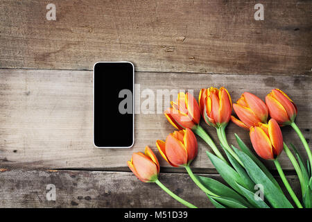 Overhead shot a blank cell phone with a bouquet of orange and yellow tulips over a wood table. Flat lay top view style. Stock Photo
