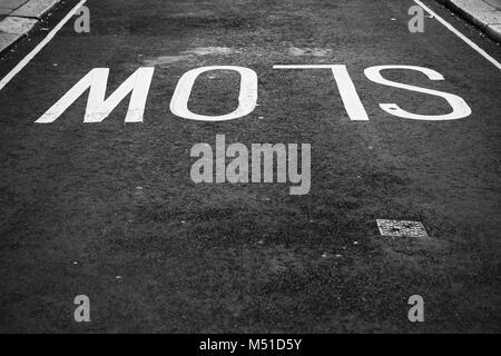 Slow, white text road marking over black urban asphalt pavement, background photo - Stock Photo