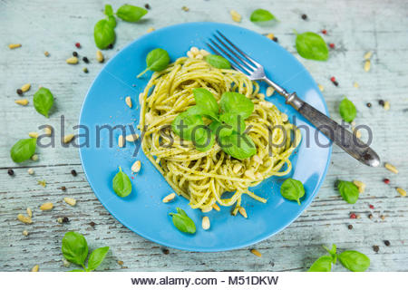Plate of cooked spaghetti pasta with green pesto - Stock Photo