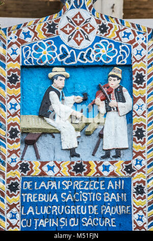 Carved wooden panel with epitaph on grave, Merry Cemetery (Cimitirul Vesel) in Sapanta, Maramures Region, Romania - Stock Photo