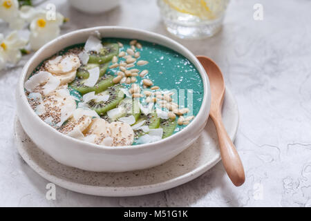 Breakfast spirulina coconut smoothie bowl topped with coconut flakes and berries - Stock Photo