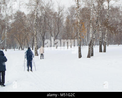 Two old people go skiing in winter Park. The view from the back - Stock Photo