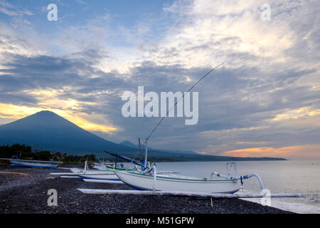 Traditional Balinese fishing boats or outrigger canoes ('jukung') on Amed Beach, with Agung volcano behind, Bali, - Stock Photo