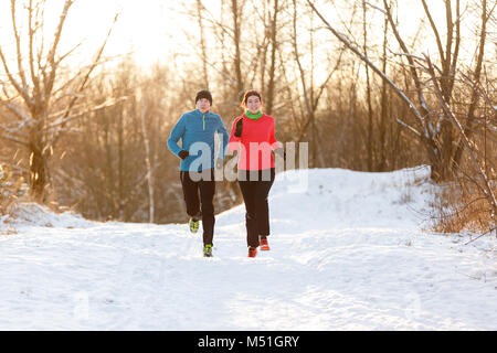 Image of running two athletes in winter park - Stock Photo