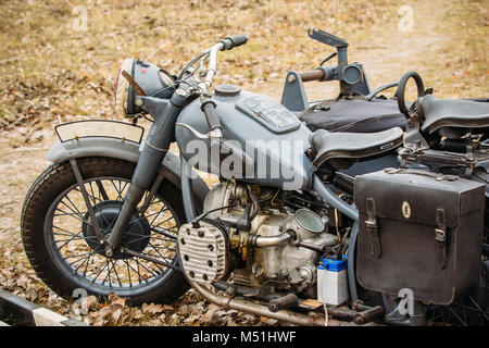 A vintage motorcycle from the times of the Second World War in gray with a stroller stands in the field. German - Stock Photo