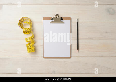 Notebook folder, pencil and measuring tape for tailor on white wood background - Stock Photo