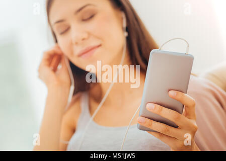 Satisfied pretty woman listening to music and closing eyes. - Stock Photo