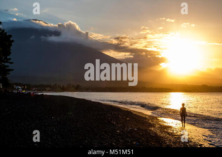 A woman walks on Amed beach with Gunung Agung volcano in the distance at sunset, Bali, Indonesia. - Stock Photo