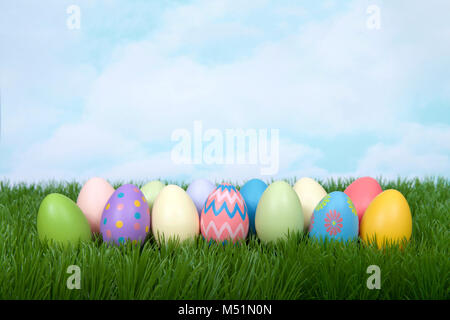 Colorful decorative and plain easter eggs lined up in a row in green grass. Blue sky with clouds in background. - Stock Photo