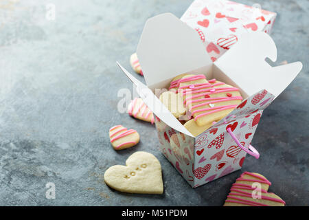 Vanilla sugar cut out cookies with pink glaze and sprinkles for Valentines Day in a treat box - Stock Photo