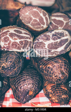 Very tasty home made smoked dried meat pieces exposed in a market, selective focus and small depth of field - Stock Photo