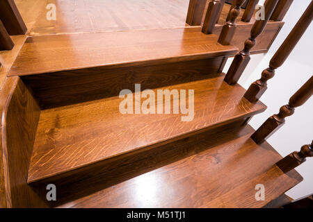 Close-up detail of brown wooden oak stairs in new renovated house. Staircase between two floors. - Stock Photo