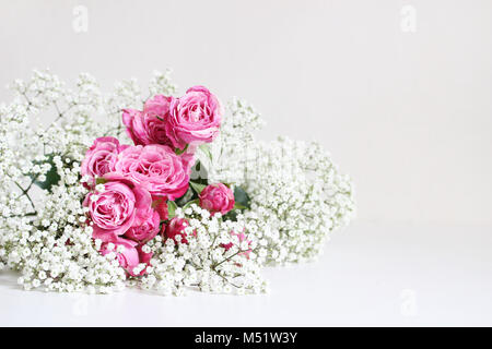 Wedding styled stock photo. Still life with pink roses and baby's breath Gypsophila flowers on white table background. - Stock Photo