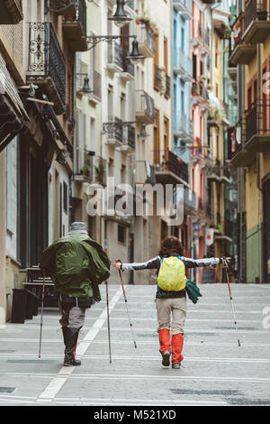 Couple of middle-aged hikers walking in street of old town, Pamplona, Navarre, Spain - Stock Photo