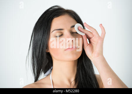 Beautiful woman cleaning her pretty face with cotton swab at her bathroom - Stock Photo