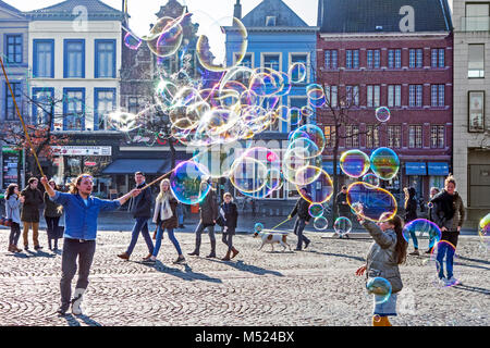 Street performer / busker blowing giant soap bubbles with loops in string held between two sticks to entertain children - Stock Photo