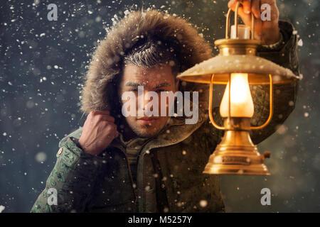 Brutal man walking under snowstorm at night lighting his way with lantern - Stock Photo