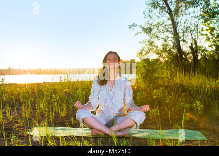 Beautiful young woman doing yoga sitting near the lake early in the morning - Stock Photo