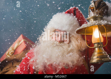 Santa Claus walking on the snow with his sack of lots of gifts and lights his way with vintage lantern. Winter night - Stock Photo