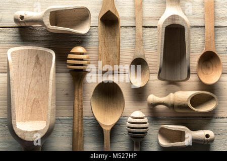 Different wooden utensils on wooden table - Stock Photo
