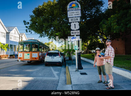 Tourists consult map at beginning point of U.S. Route 1. US 1 travels along the east coast of Florida, beginning - Stock Photo