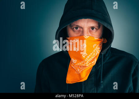 Portrait of masked criminal male person looking at camera. Adult man with hoodie and scarf over face as bandit or - Stock Photo