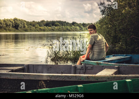 Teenager boy lonely contemplation countryside landscape on river bank during countryside summer holidays - Stock Photo