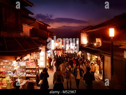 Matsubara dori street in Kyoto at night with brightly lit souvenir shop displays, signs and street lights. Busy - Stock Photo