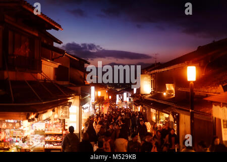 Twilight old Kyoto city scenery at Matsubara dori street in fall with brightly lit shops and street lights, crowded - Stock Photo