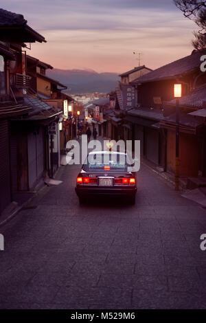 Early morning taxi cab on Matsubara dori empty street in Kyoto before sunrise in autumn near Kiyomizu-dera temple. - Stock Photo