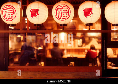 People dining inside a traditional Japanese restaurant with lanterns lit up at night. Gion, Kyoto, Japan 2017. - Stock Photo