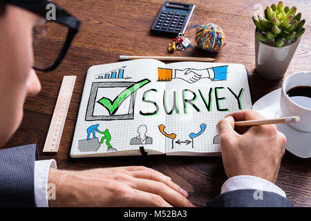 Man Drawing Customer Satisfaction Survey Concept In Notepad - Stock Photo
