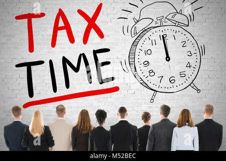 Group Of Diverse People Looking At Tax Time Words - Stock Photo