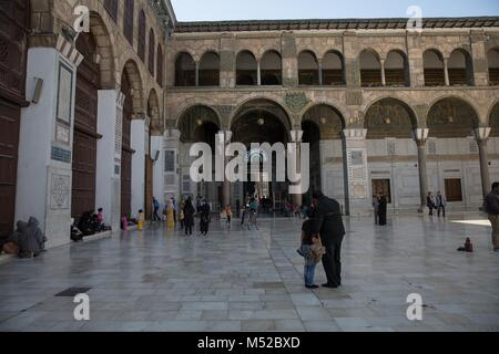 Families leave Damascus' Umayyad Mosque after Friday prayers. Despite the ongoing conflict in Syria, life in government - Stock Photo