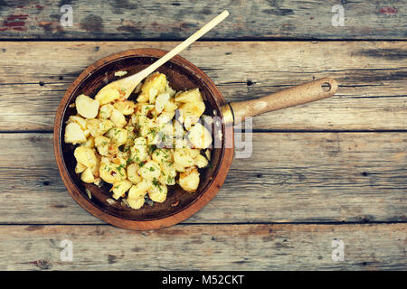 Fried potatoes in a frying pan on a wooden table - Stock Photo