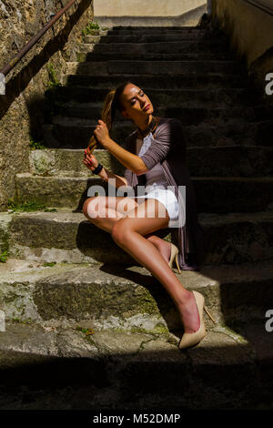 Yopung woman legs heels ponytail pony-tail fair hair skimpy clothing - Stock Photo