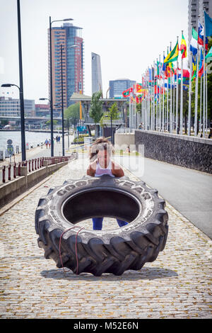 Photo of an attractive young woman working out with a tractor tire in Rotterdam, The Netherlands - Stock Photo