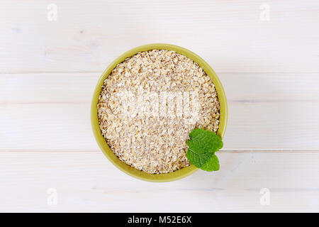 dry rolled oatmeal in a green bowl - Stock Photo