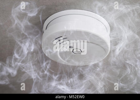 Close-up Of A Smoke Detector On Ceiling Surrounded By Smoke - Stock Photo