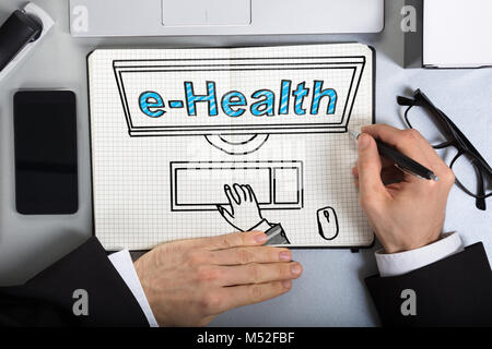 Elevated View Of A Business Man Drawing E-health Concept On Squared Paper Sheet At Office - Stock Photo