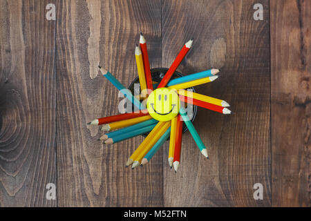 Multicolored pencils in a stand on a wooden school desk - Stock Photo